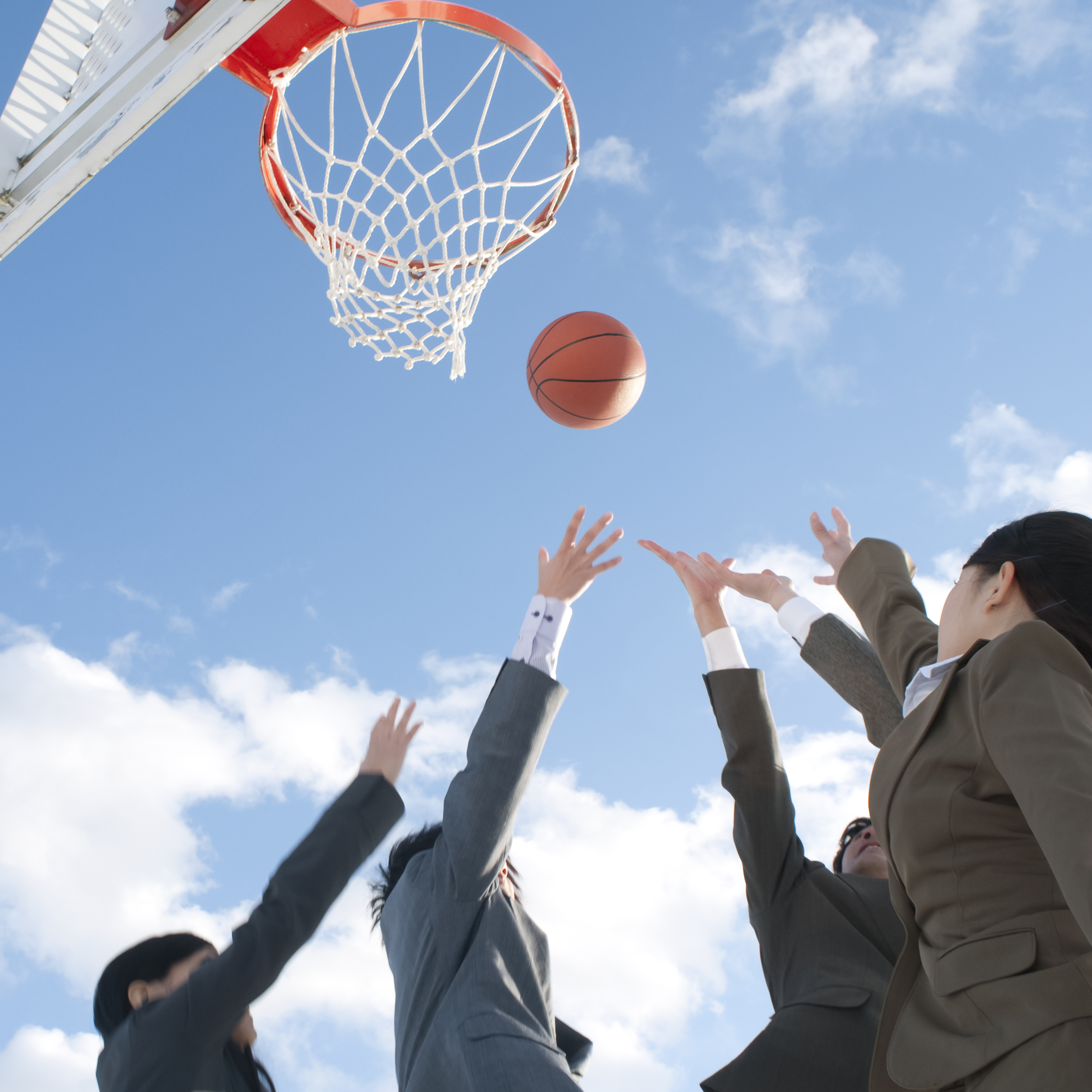 Photo of people in business suits reaching up toward a basketball that is in the air near a basketball hoop.