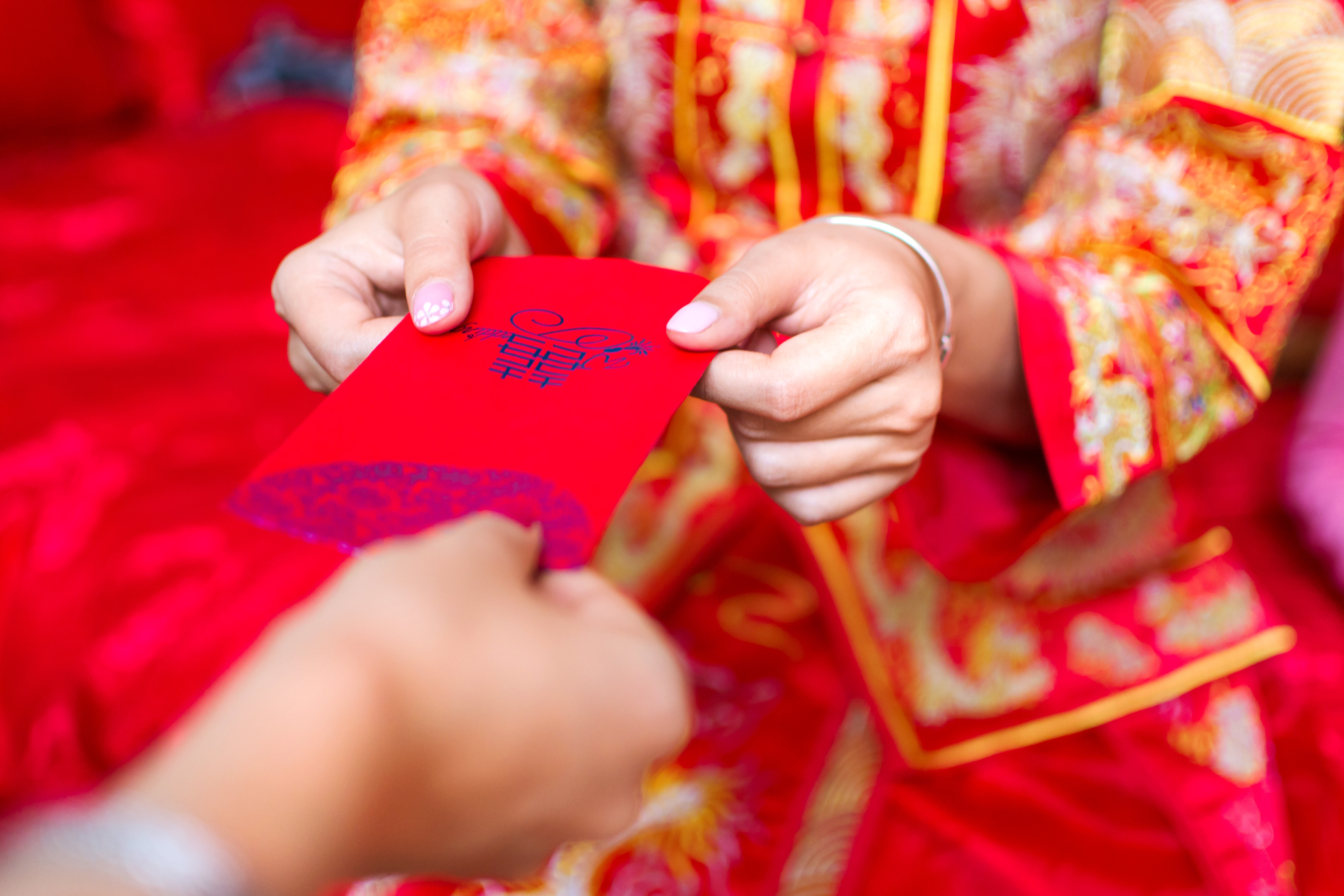 Person in bright embroidered red and yellow clothing handing red envelope to another persion.
