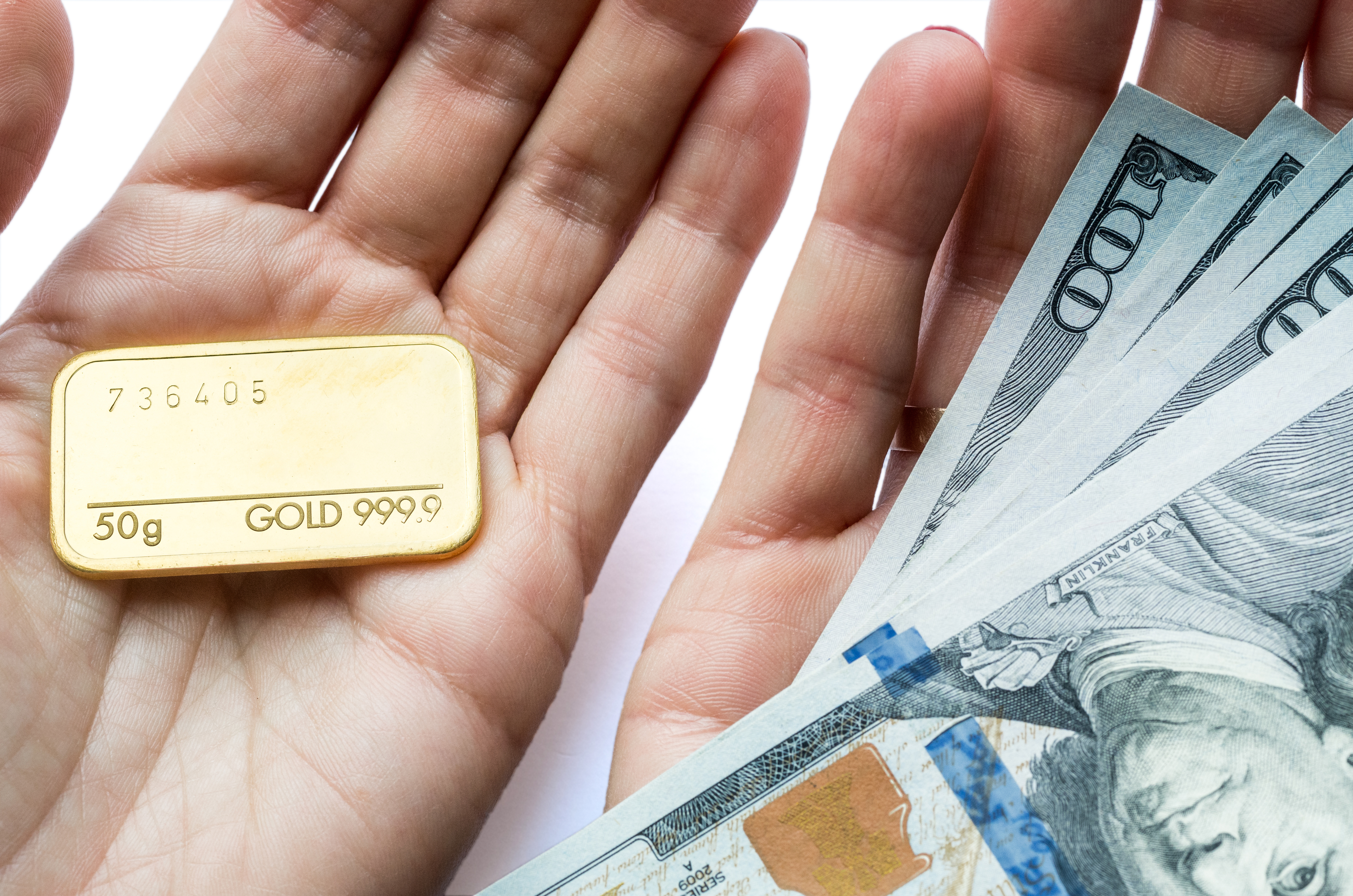 Person holding gold bullion in one hand and $100 bills in the other.