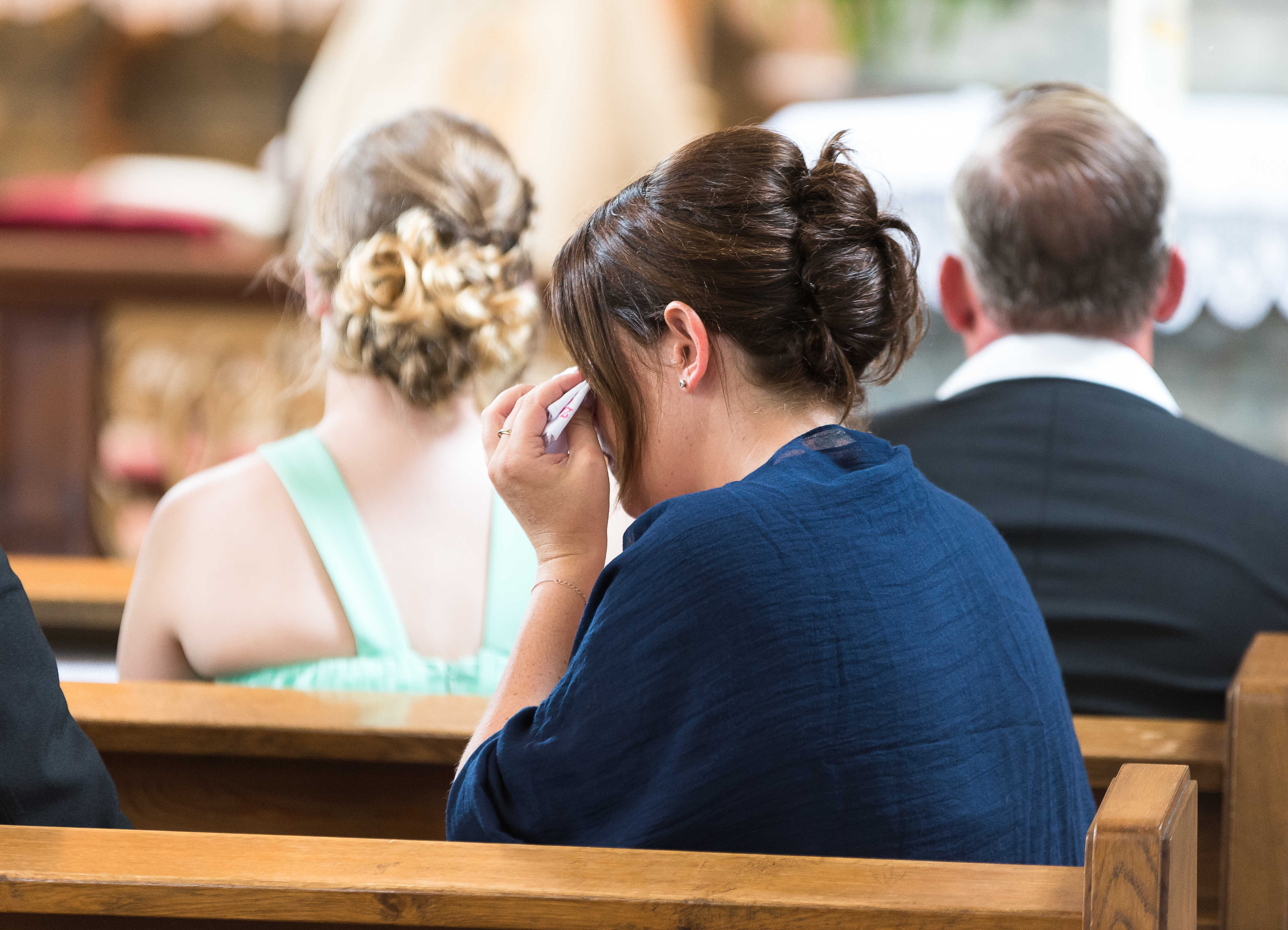Woman wiping her eyes with tissue, sitting in church pew behind two other people.