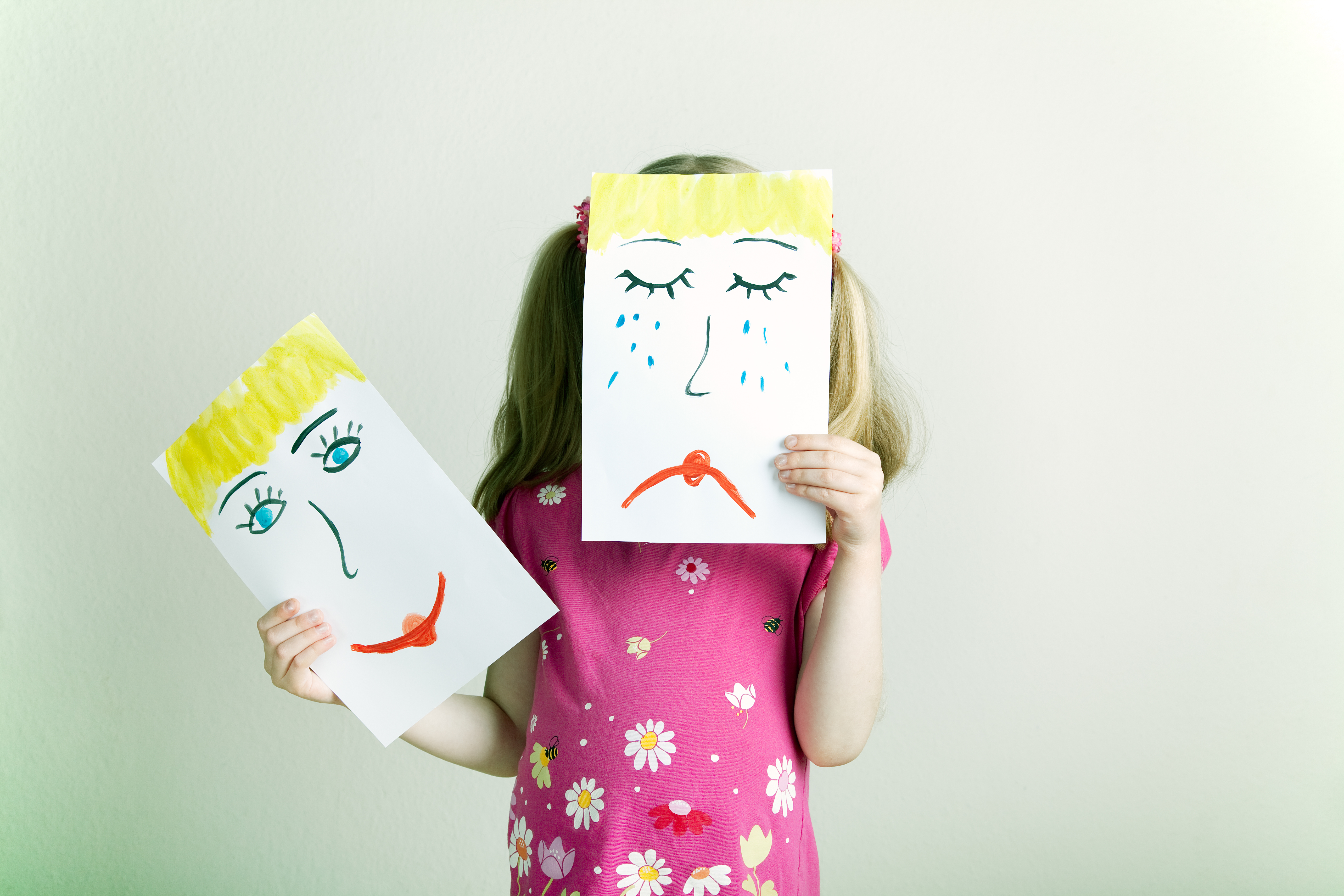 Child in pink floral shirt holding a drawing of a crying face in front of their own face and a drawing of a happy face in their free hand.