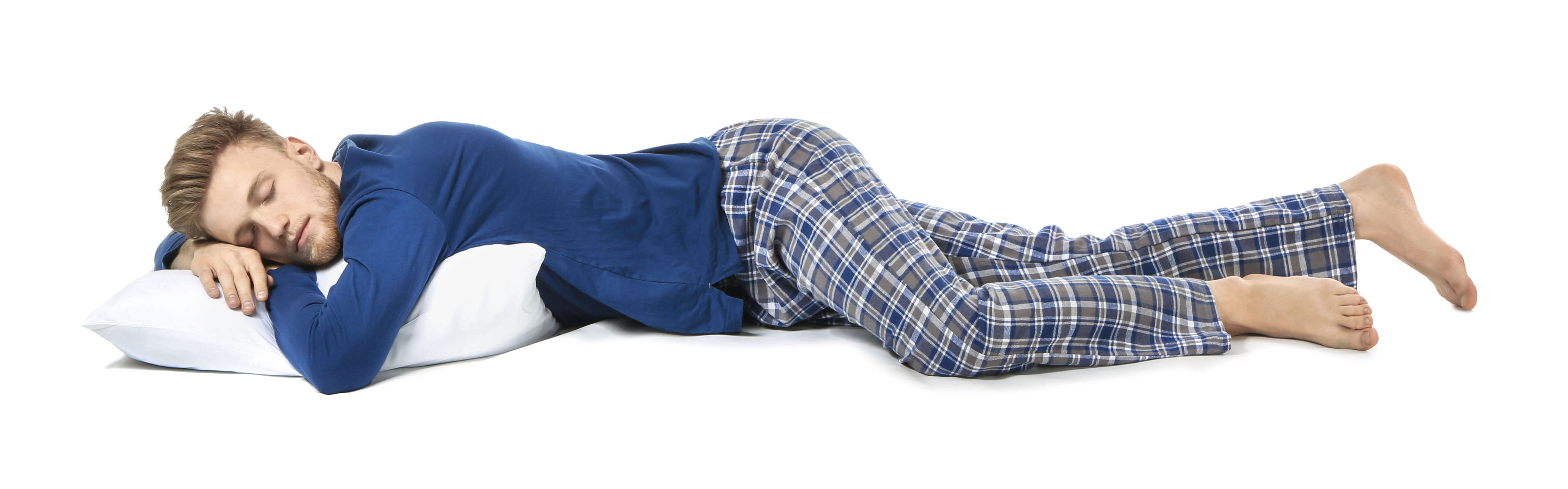 Image of a young man in a blut t-shirt and blue/gray plaid pajama pants lying asleep on a white pillow. Background of image is white.