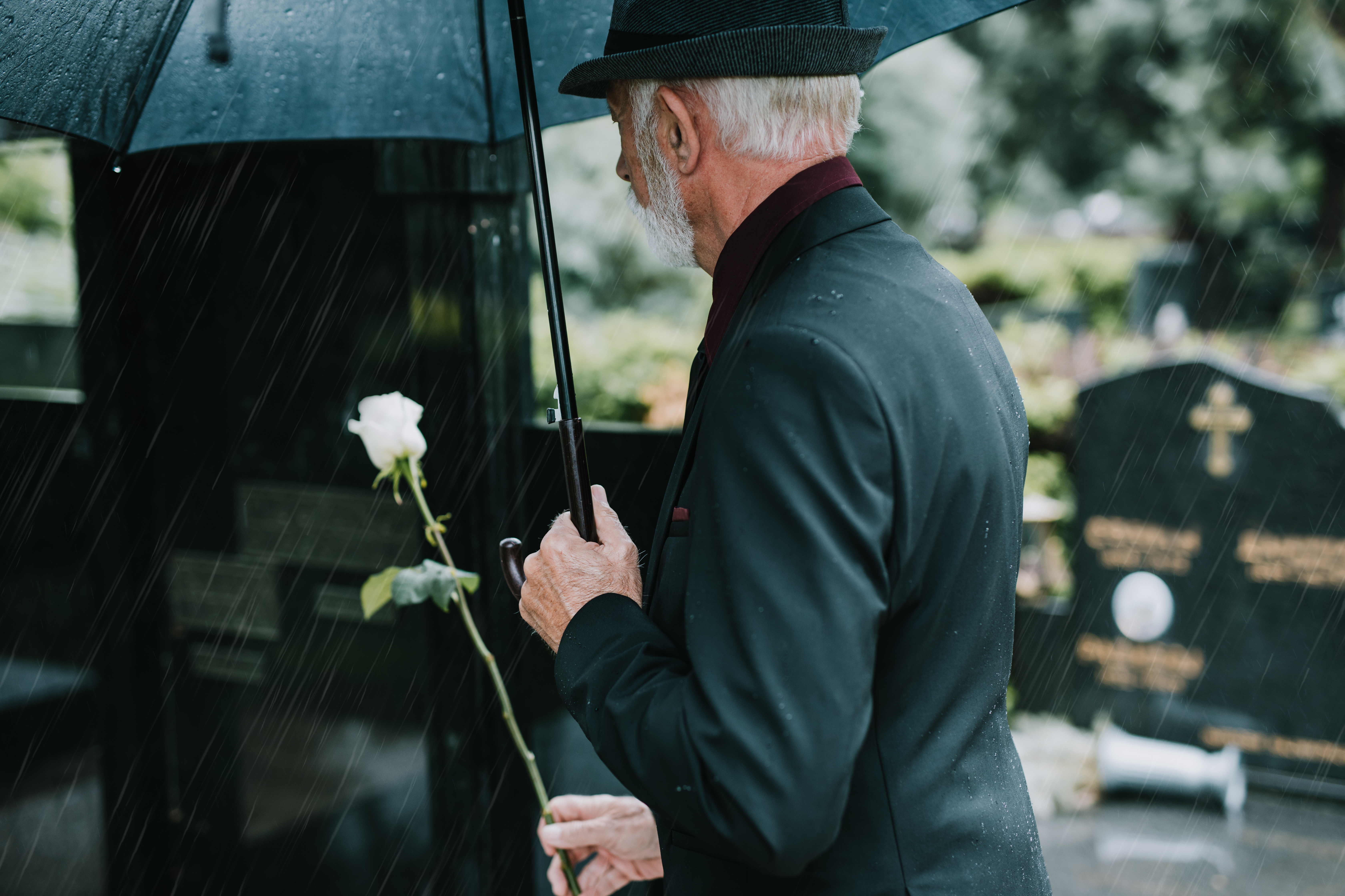 Man with white hair and beard, wearing black suit and hat, holding black umbrella and white flower, standing near gravestones.
