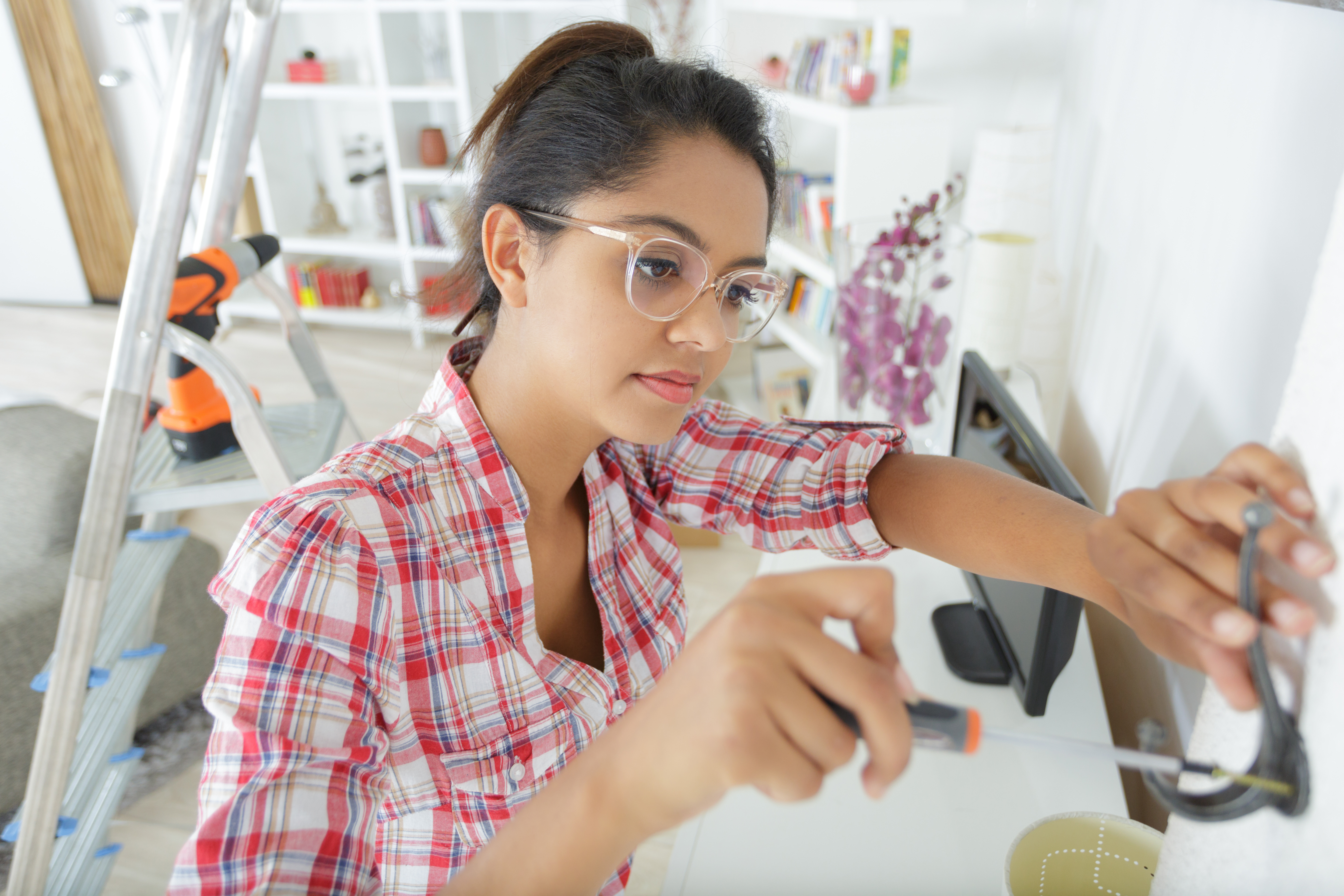 Photo: woman in plaid blouse screws a coat hook into the wall of her home. In the background are her desk with computer, bookshelves, and a ladder with power drill.