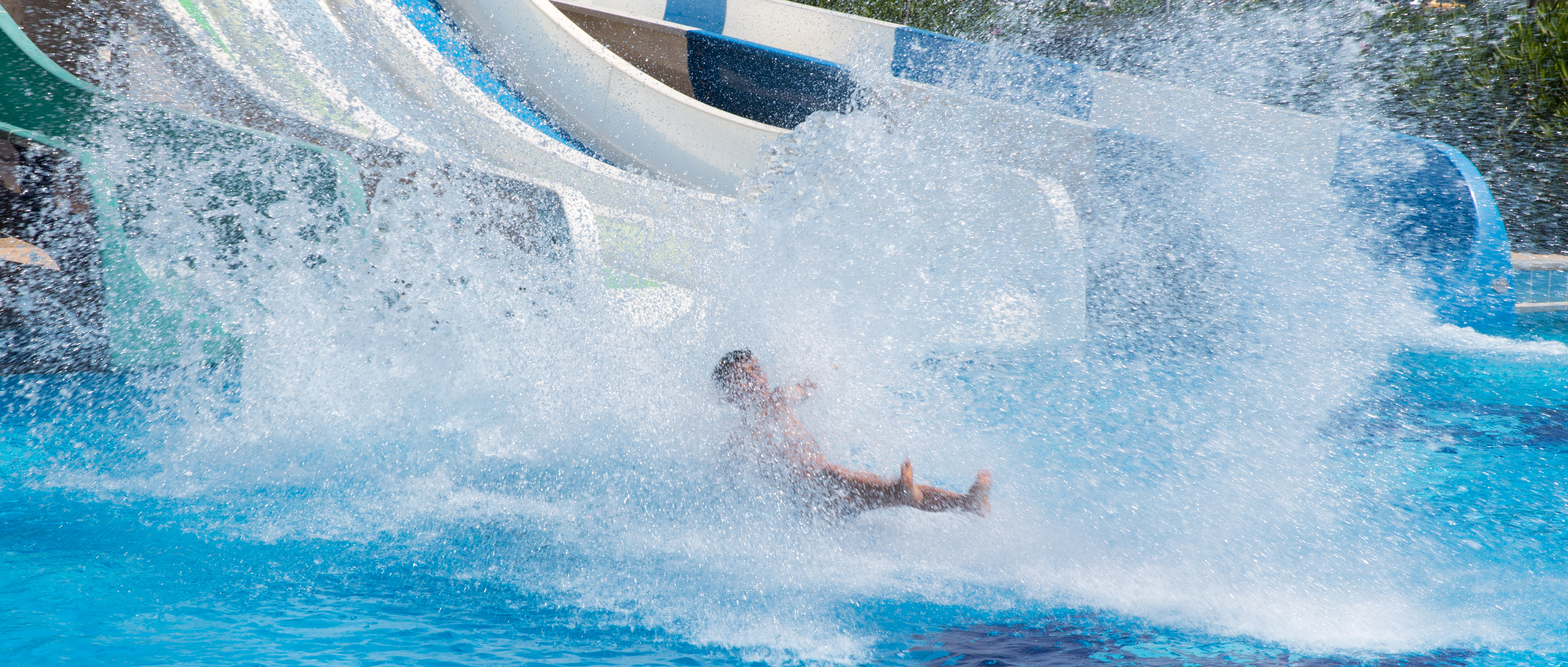 The Markets Corner: Water. A person splashes into the pool at the bottom of a waterslide.