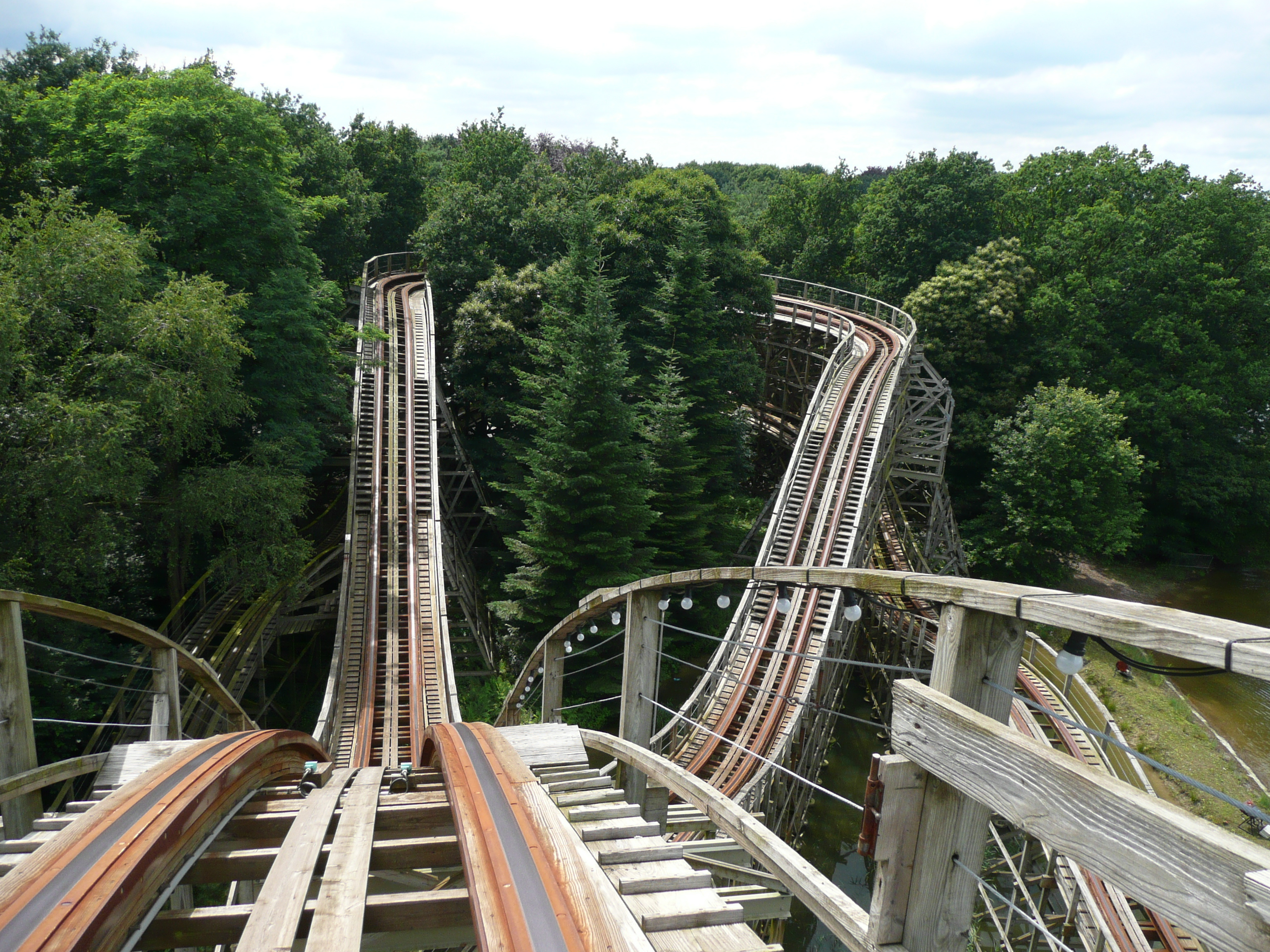 View of a wooden roller coaster track among green trees from the viewpoint of a person riding in the front car.