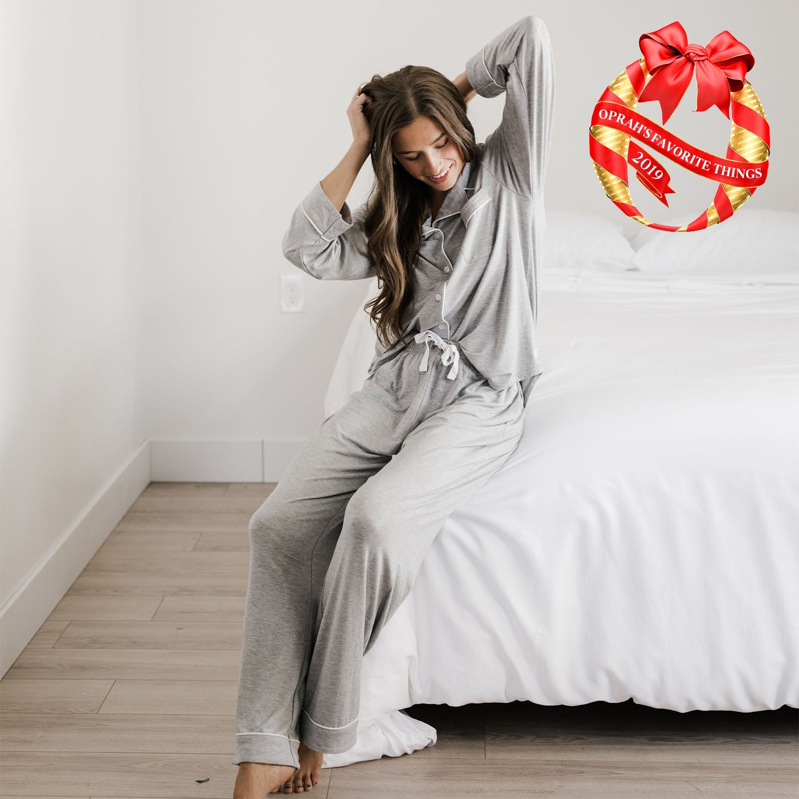 "Person with long hair sitting on white bed wearing gray knit pajamas; illustrated ""Oprah's Favorite Things"" seal in upper right corner of image."