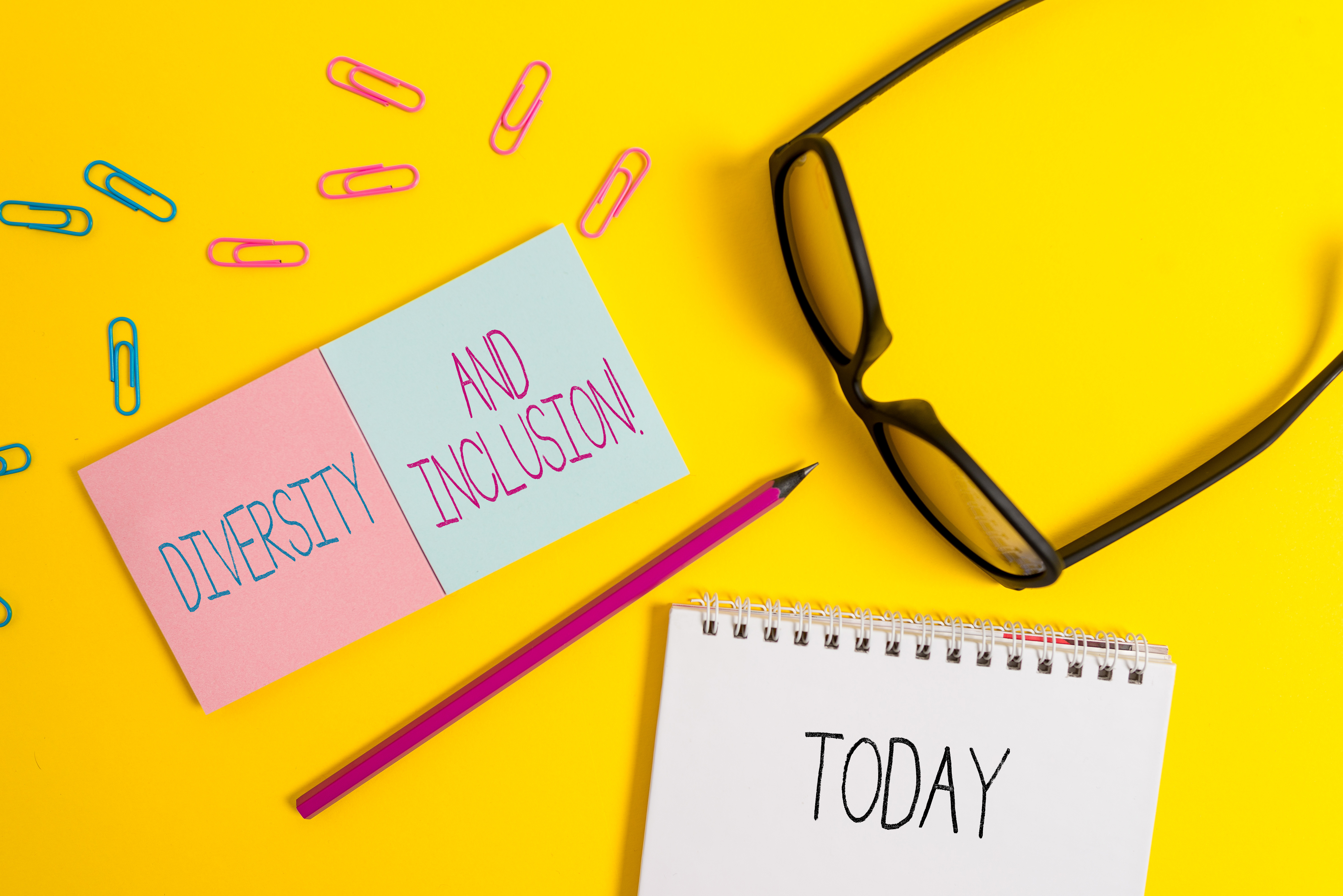 "Yellow background with glasses, pencil, paper clips, and notepads saying, ""DIVERSITY AND INCLUSION TODAY!"""