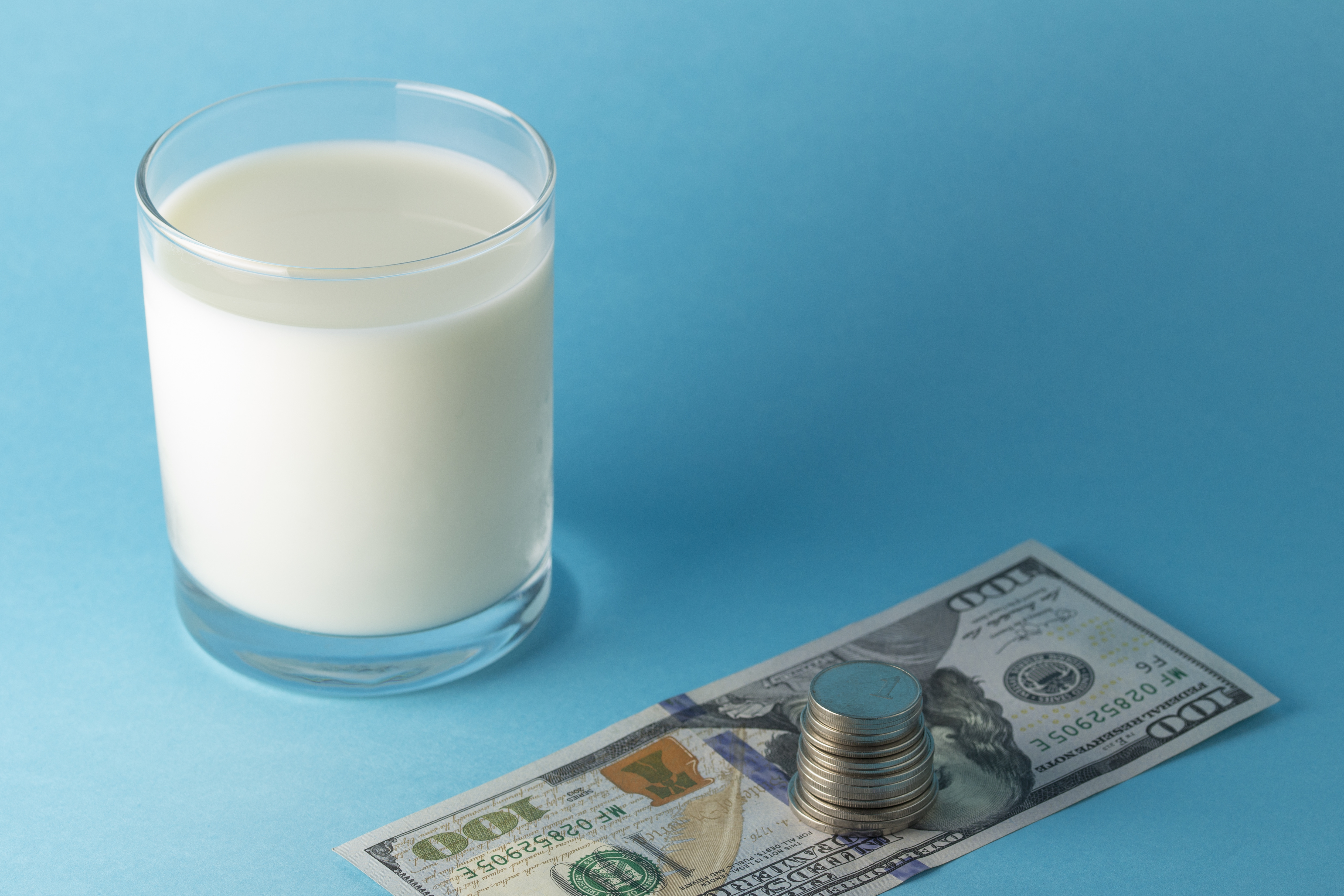 Glass of milk on a light blue surface, next to a U.S. $100 pill with a stack of coins set atop it.